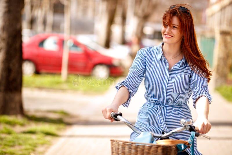 Ritratto della donna sul viaggio della bici nella città fotografia stock