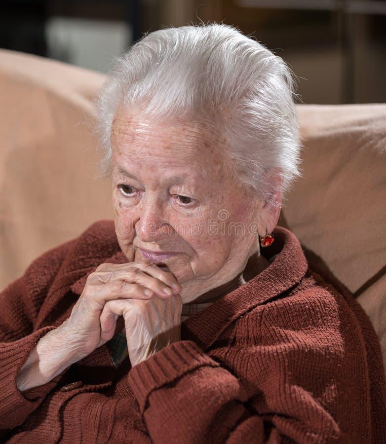 Ritratto della donna triste dai capelli grigi anziana fotografia stock