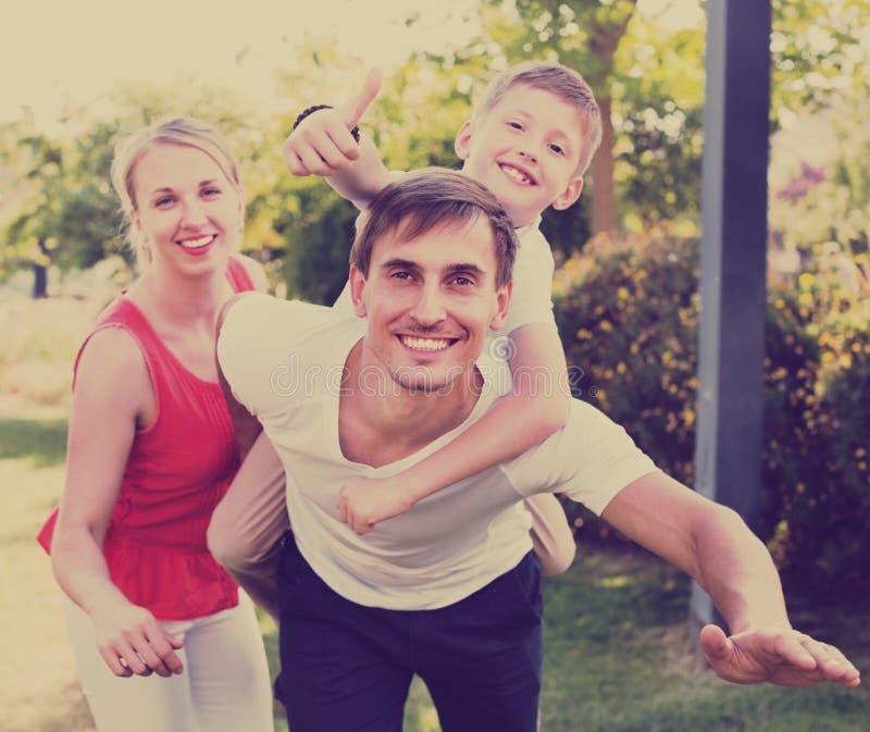 Ritratto della famiglia allegra con il ragazzo che si siede sulla parte posteriore del ` s del padre immagini stock libere da diritti