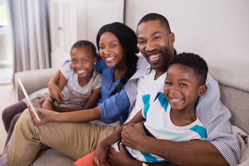 Ritratto della famiglia allegra facendo uso della compressa digitale mentre sedendosi sul sofà fotografia stock libera da diritti