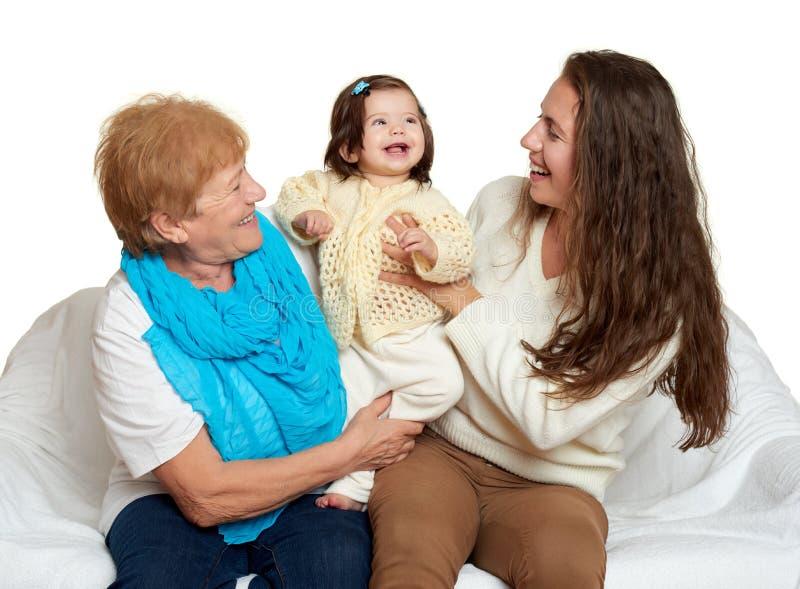 Ritratto della famiglia - bambini con la madre e la nonna Il fondo bianco, gente felice si siede sul sofà fotografie stock