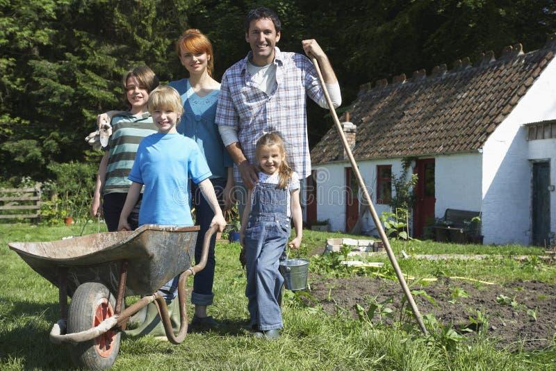 Ritratto della famiglia che fa il giardinaggio fuori del cottage fotografie stock libere da diritti