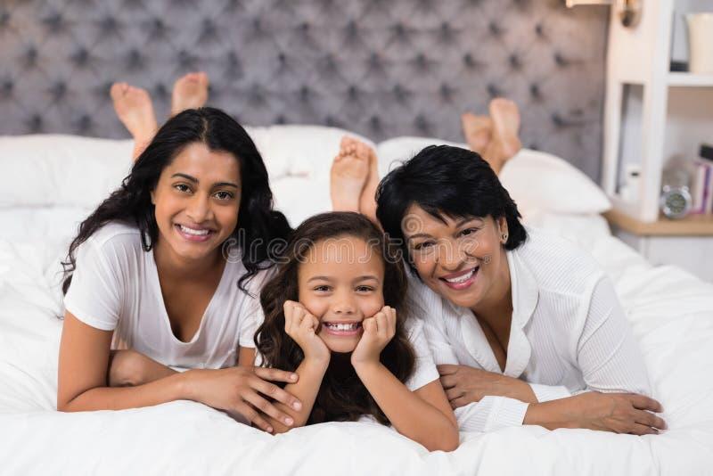 Ritratto della famiglia di diverse generazioni allegra che si trova sul letto fotografie stock libere da diritti