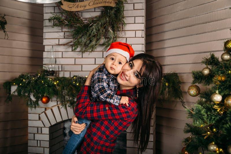 Ritratto della famiglia di Natale del ragazzino sorridente felice in cappello rosso di Santa in mani del ` s della madre Concetto fotografia stock