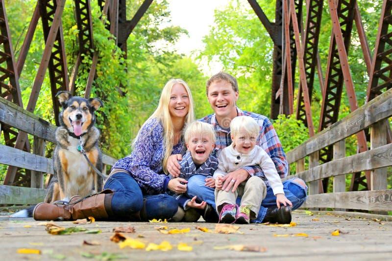 Ritratto della famiglia e del cane felici fuori nella caduta immagini stock libere da diritti