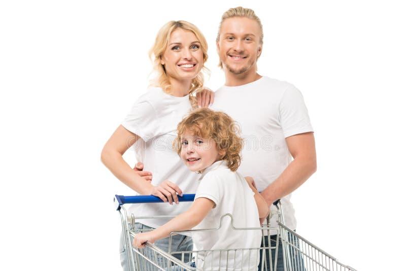 ritratto della famiglia felice con il figlio in carrello che esamina macchina fotografica immagini stock libere da diritti