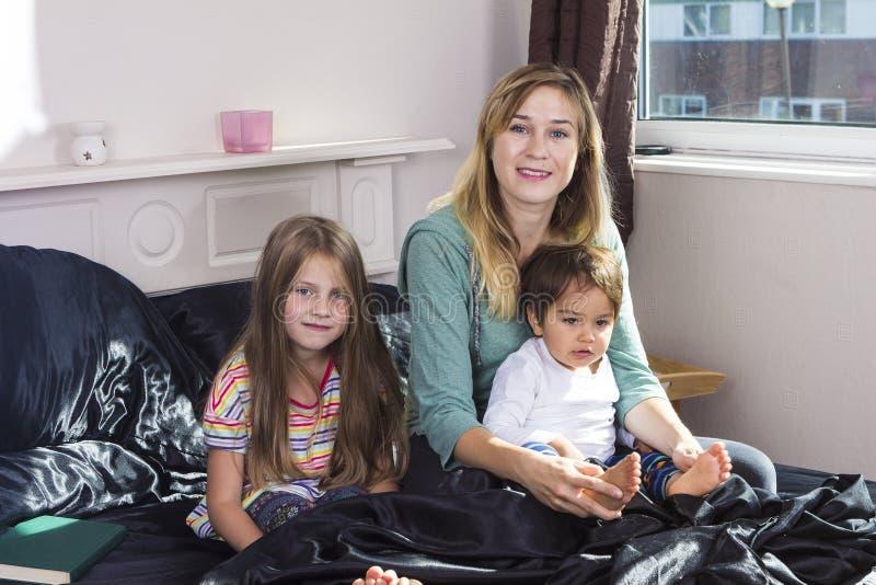 Ritratto della famiglia a letto a casa fotografia stock libera da diritti
