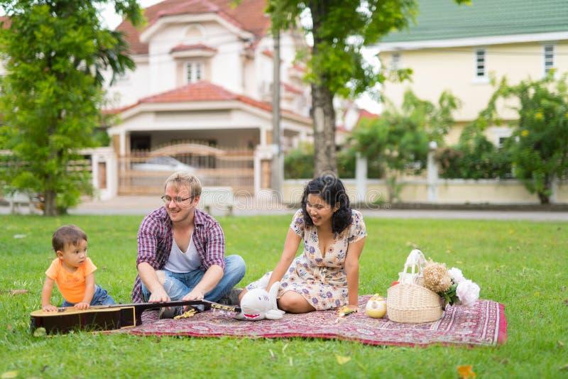 Ritratto della famiglia multi-etnica felice che lega insieme all'aperto fotografia stock libera da diritti