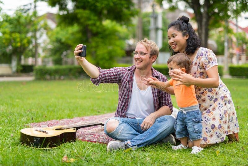 Ritratto della famiglia multi-etnica felice che prende insieme selfie all'aperto fotografie stock libere da diritti