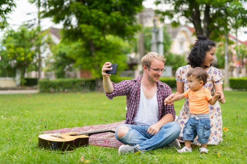 Ritratto della famiglia multi-etnica felice che prende insieme selfie all'aperto fotografia stock libera da diritti