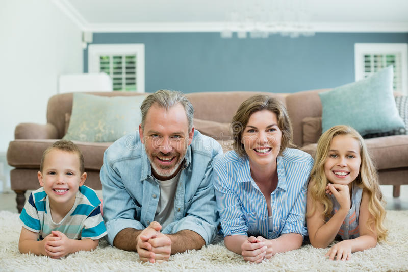 Ritratto della famiglia sorridente che si trova insieme sul tappeto in salone fotografia stock libera da diritti