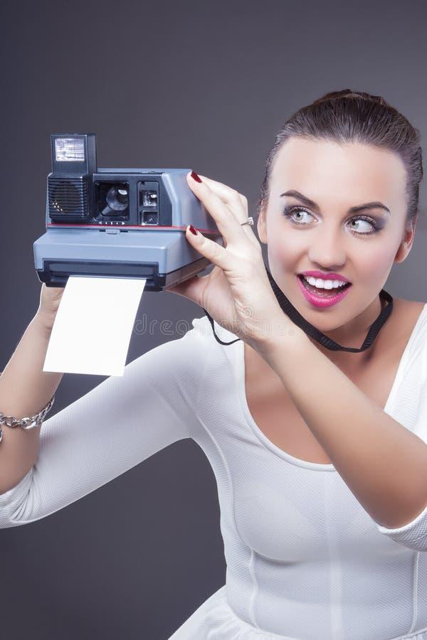 Ritratto della femmina castana caucasica sorridente con Camer istantaneo fotografie stock