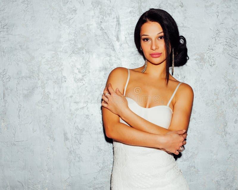 Ritratto della femmina sexy castana in vestito bianco sopra la parete grigia fotografia stock libera da diritti