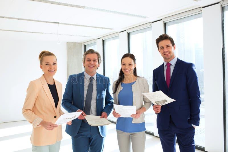 Ritratto della gente di affari sorridente con i documenti in ufficio immagine stock libera da diritti