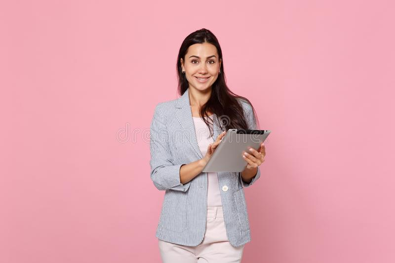 Ritratto della giovane donna affascinante sorridente in rivestimento a strisce facendo uso del computer del pc della compressa is fotografia stock