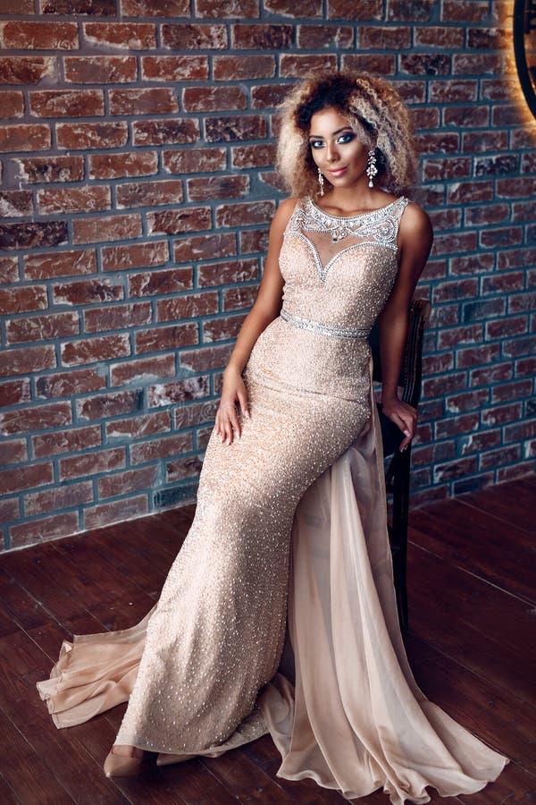 Ritratto della giovane donna afroamericana attraente in vestito stretto dall'oro in un appartamento di lusso Bellezza e concetto  immagine stock
