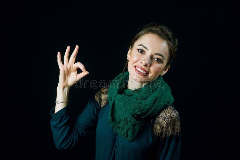 Ritratto della giovane donna allegra che mostra il pozzo di gesto fotografia stock