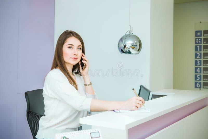 Ritratto della giovane donna amichevole che esamina macchina fotografica, parlante sul telefono dietro la reception Amministrator immagine stock