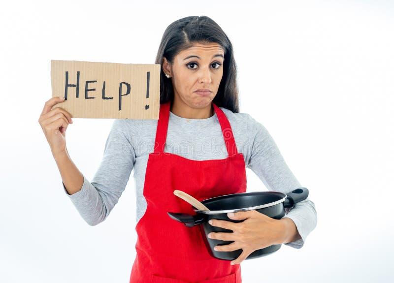 Ritratto della giovane donna attraente che cucina indossando un grembiule rosso che tiene un segno di aiuto immagini stock libere da diritti