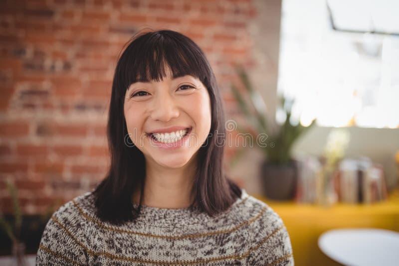 Ritratto della giovane donna attraente sorridente che sta contro il muro di mattoni immagine stock