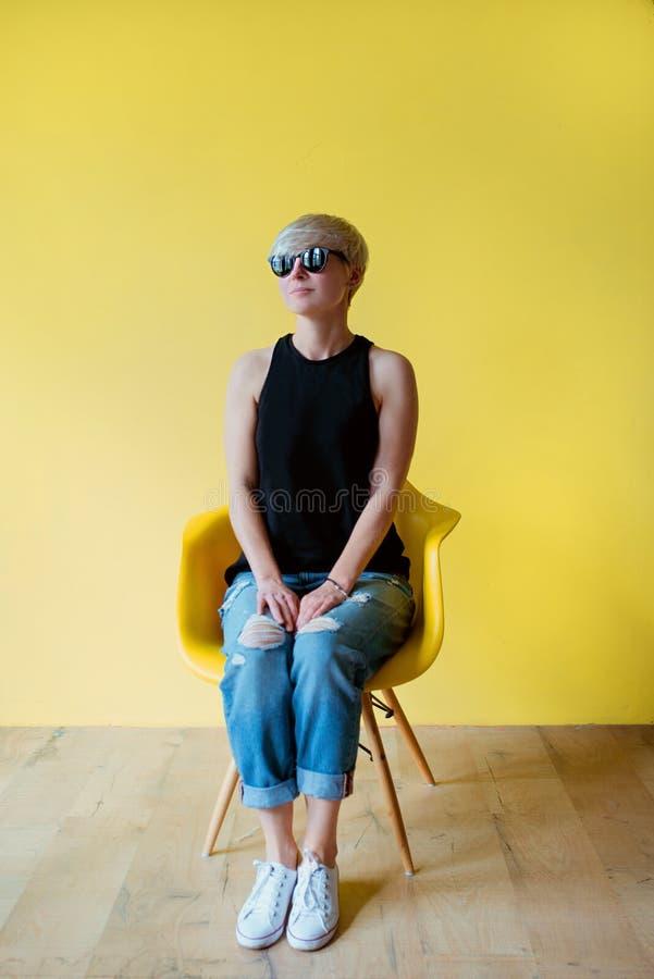 Ritratto della giovane donna bionda alla moda che si siede sulla sedia gialla sul backgrou giallo della parete fotografia stock libera da diritti