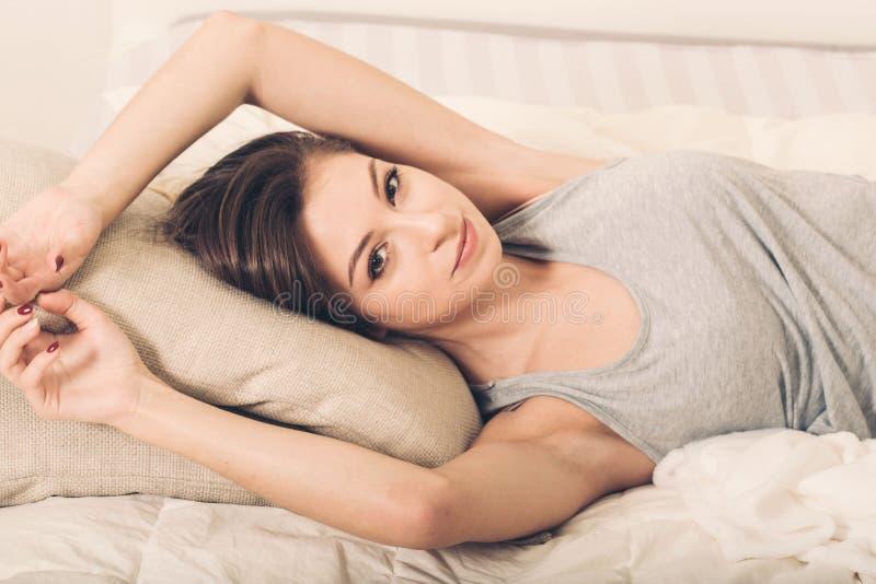 Ritratto della giovane donna in camera da letto sulla macchina fotografica di sguardo di rilassamento sola del letto immagini stock libere da diritti