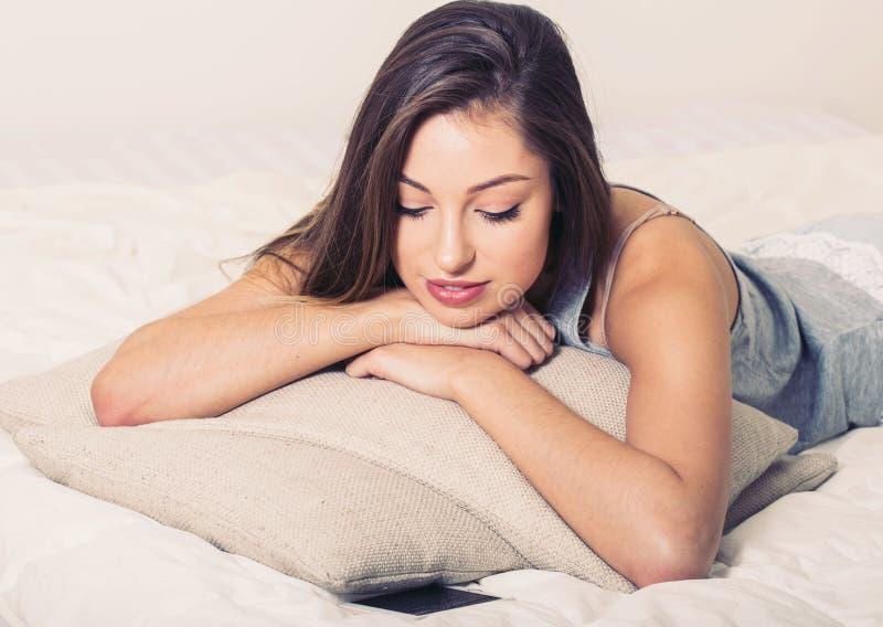 Ritratto della giovane donna in camera da letto sulla macchina fotografica di sguardo di rilassamento sola del letto fotografia stock