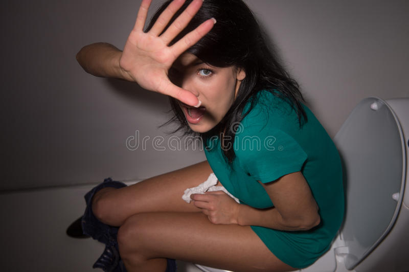 Ritratto della giovane donna che grida nella toilette alla macchina fotografica fotografie stock libere da diritti