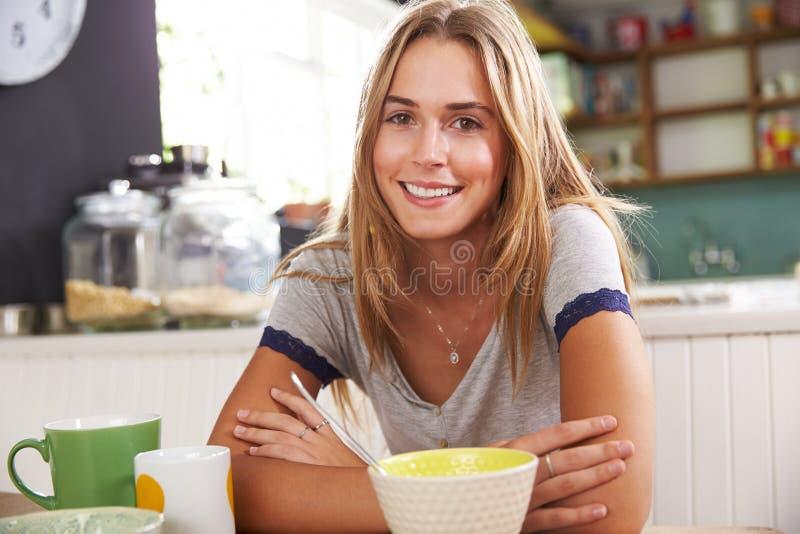 Ritratto della giovane donna che mangia prima colazione in cucina fotografia stock libera da diritti