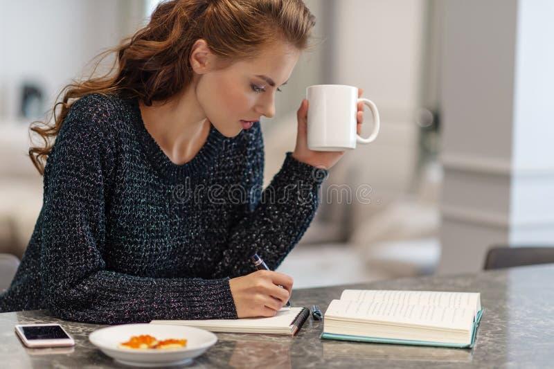Ritratto della giovane donna che si siede alla scrittura della tavola in libro fotografie stock libere da diritti