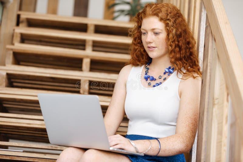 Ritratto della giovane donna che si siede alle scale in ufficio immagini stock