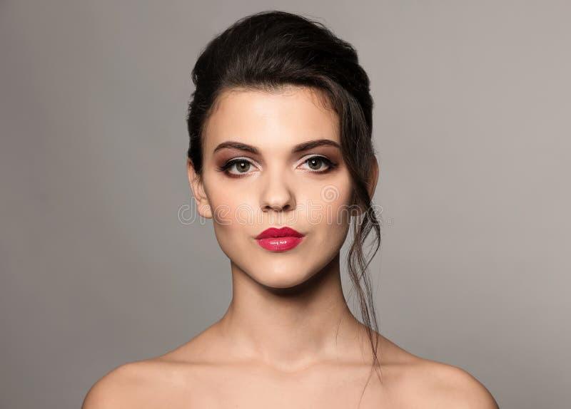Ritratto della giovane donna con bello trucco professionale su fondo grigio fotografie stock libere da diritti