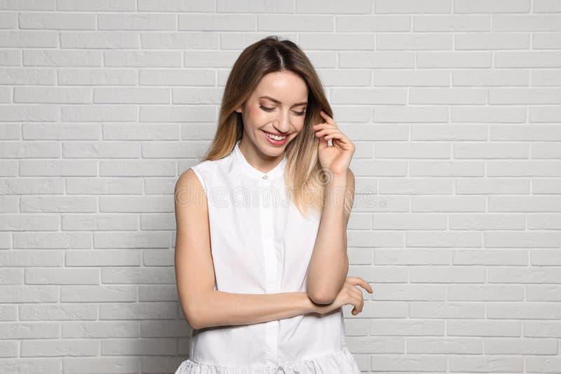 Ritratto della giovane donna con il bello fronte vicino al muro di mattoni fotografie stock libere da diritti