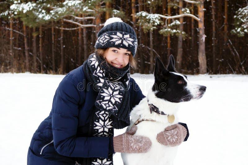 Ritratto della giovane donna con il suo cane in bianco e nero su un fondo della foresta di conifere di inverno fotografia stock libera da diritti