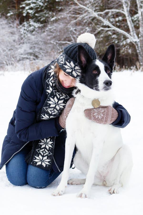 Ritratto della giovane donna con il suo cane in bianco e nero su un fondo della foresta di conifere di inverno fotografie stock libere da diritti