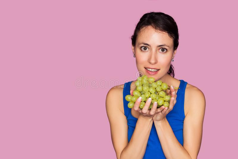 Ritratto della giovane donna con l'uva fresca isolata su fondo rosa immagine stock