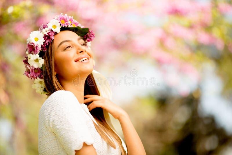 Ritratto della giovane donna con la corona dei fiori freschi sulla testa immagine stock libera da diritti
