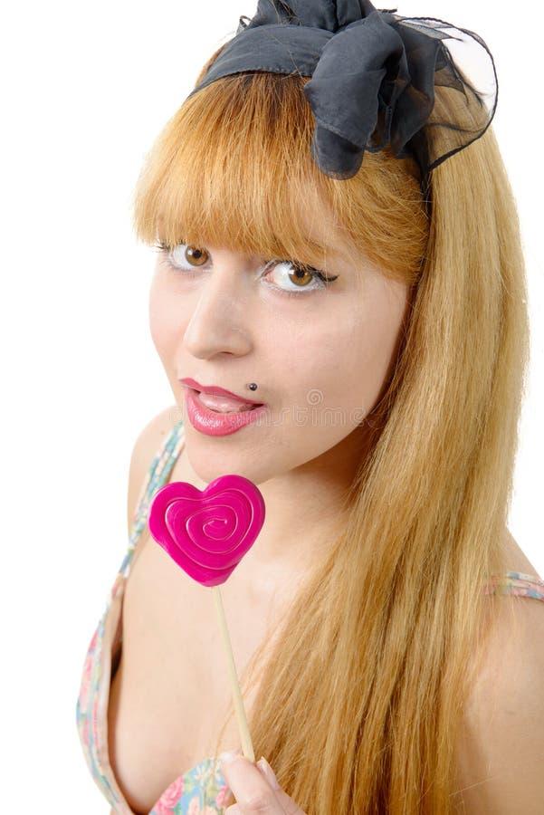 Ritratto della giovane donna con la lecca-lecca di forma del cuore fotografie stock libere da diritti