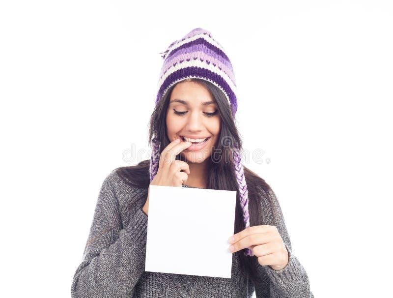 Ritratto della giovane donna con una carta di tenuta di lana del segno del cappello peruviano e del maglione Priorit? bassa bianc immagine stock libera da diritti
