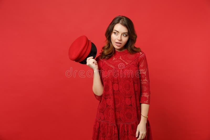 Ritratto della giovane donna curiosa stupita in vestito dal pizzo che tiene berretto in mano sguardo da parte isolato sulla paret fotografia stock libera da diritti