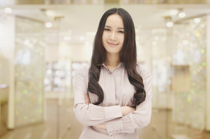 Ritratto della giovane donna dai capelli lunghi sorridente con le armi attraversate e che esaminano macchina fotografica, all'inte immagini stock