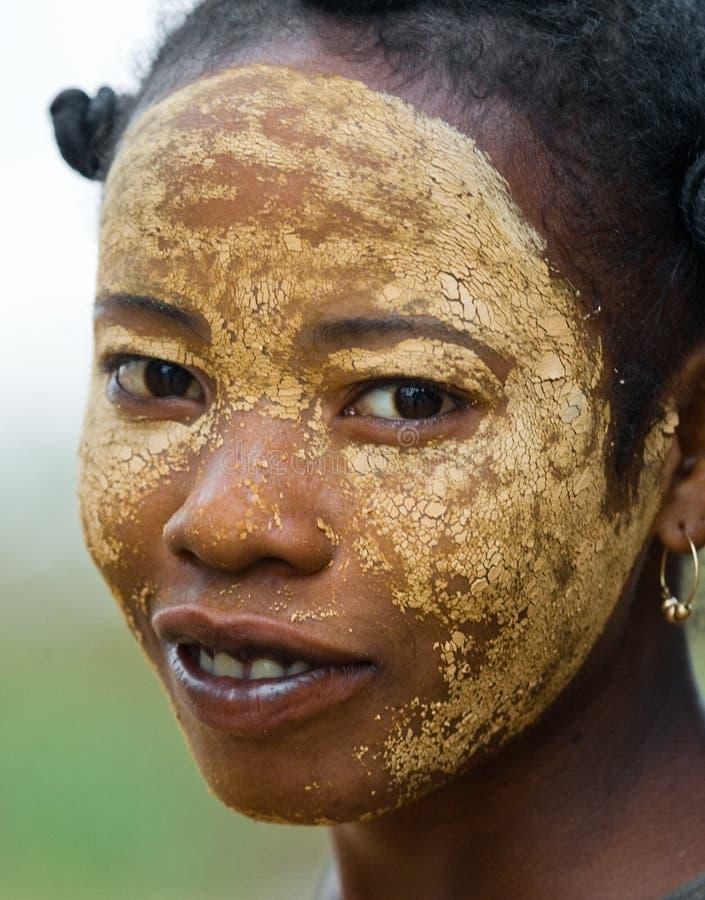 Ritratto della giovane donna dal villaggio in una maschera dell'argilla su un fronte fotografie stock