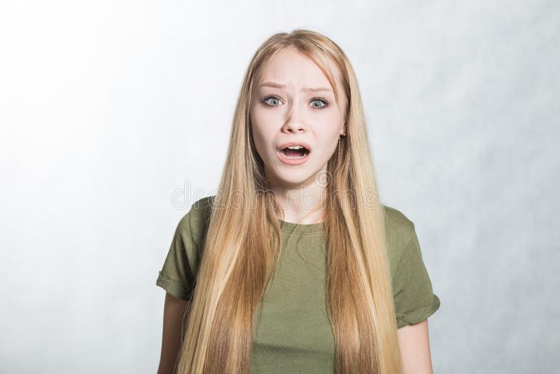Ritratto della giovane donna di grido arrabbiata sui precedenti grigi immagine stock