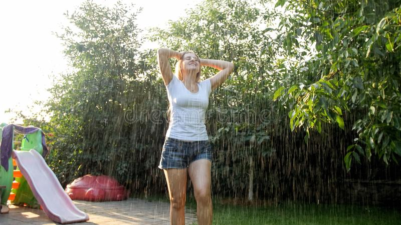 Ritratto della giovane donna di risata felice con capelli lunghi in vestiti bagnati che ballano sotto la pioggia calda in giardin immagine stock