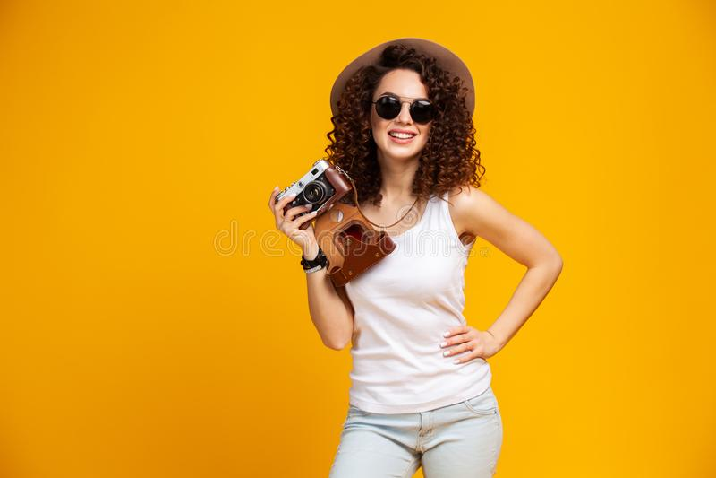 Ritratto della giovane donna di risata in occhiali che prendono le immagini sulla retro macchina fotografica d'annata della foto  immagine stock