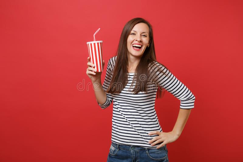 Ritratto della giovane donna di risata in vestiti a strisce casuali che tengono tazza di plastica di cola o di soda isolata su ro fotografie stock libere da diritti