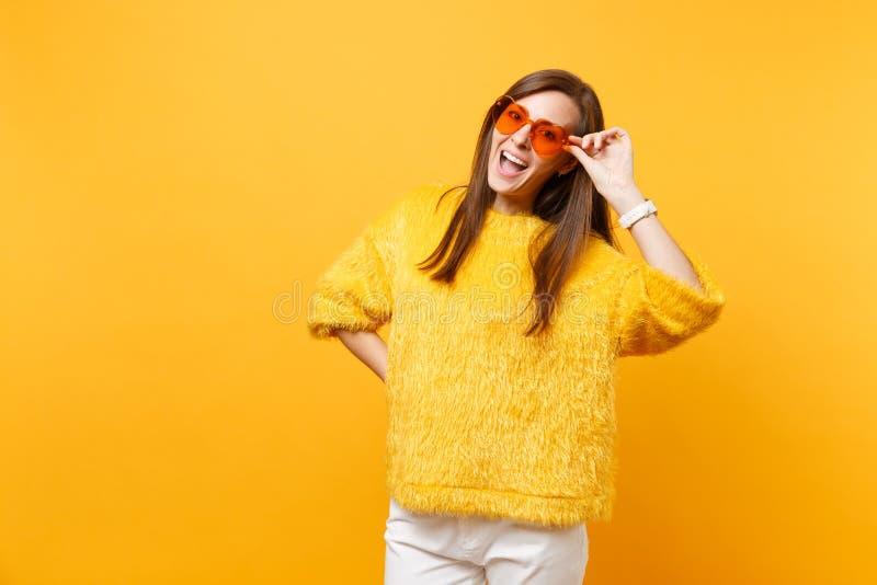 Ritratto della giovane donna divertente allegra in maglione della pelliccia, pantaloni bianchi che giudicano gli occhiali arancio immagine stock