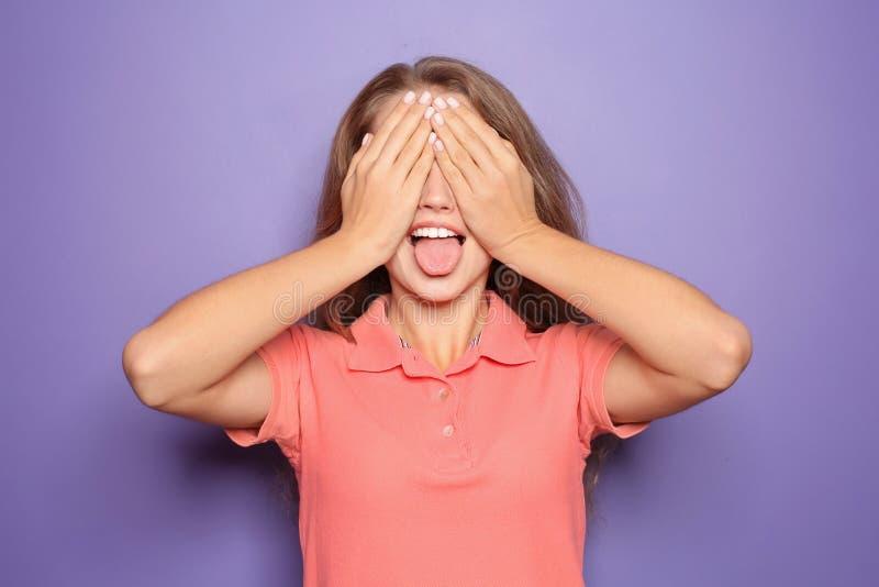 Ritratto della giovane donna divertente che copre gli occhi di sue mani sul fondo di colore fotografie stock