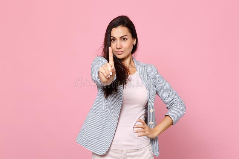 Ritratto della giovane donna divertente in rivestimento a strisce che guarda, indicante i dito indice da parte isolati sul fondo  immagini stock