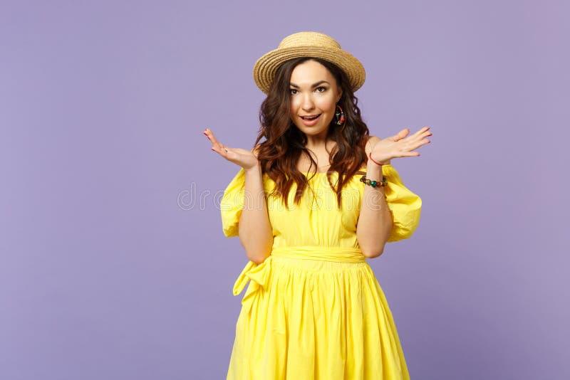 Ritratto della giovane donna emozionante in vestito giallo, mani di diffusione del cappello di estate, guardanti macchina fotogra immagini stock